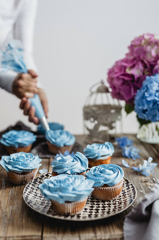 Woman is decorating cupcakes by Tatjana Zlatkovic for Stocksy United