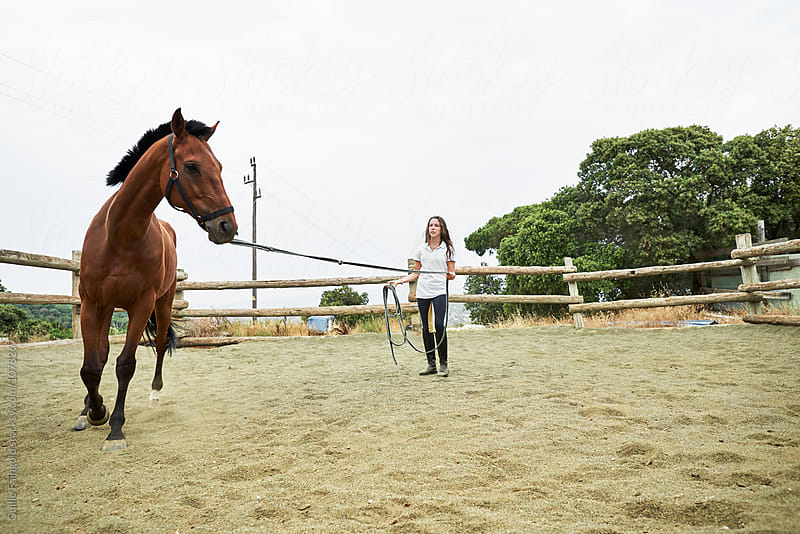 brunette jockey training her horse on paddock by Guille Faingold for Stocksy United