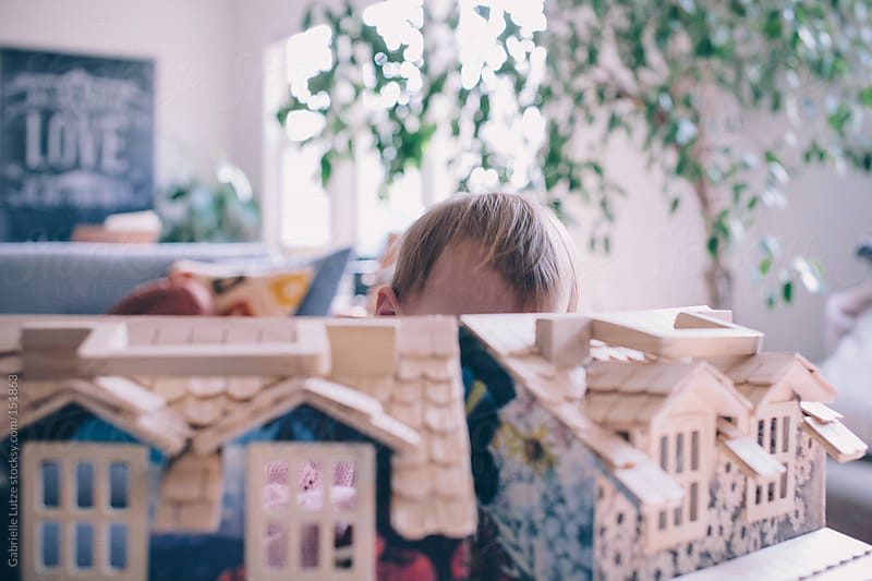 Little Girl Playing with a Dollhouse  by Gabrielle Lutze for Stocksy United