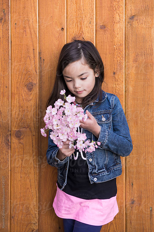 Little Girl With Pink Cherry Blossoms by Ronnie Comeau for Stocksy United