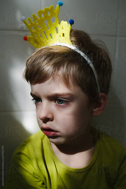 Close up of sad birthday boy sitting in bathroom. by Julia Forsman for Stocksy United