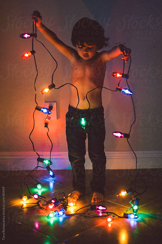 a little boy holds a string of holiday lights by Tara Romasanta for Stocksy United