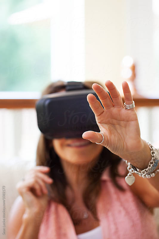 VR: Mature Woman Reaches Out While Wearing Virtual Reality Headset by Sean Locke for Stocksy United