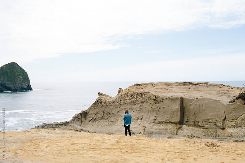 Woman standing on the edge of a rocky terrain overlooking the ocean by KATIE + JOE for Stocksy United