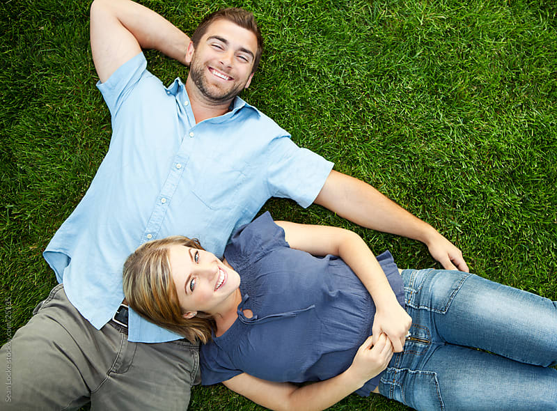 Grass: Young Couple Laying Together on Grass by Sean Locke for Stocksy United