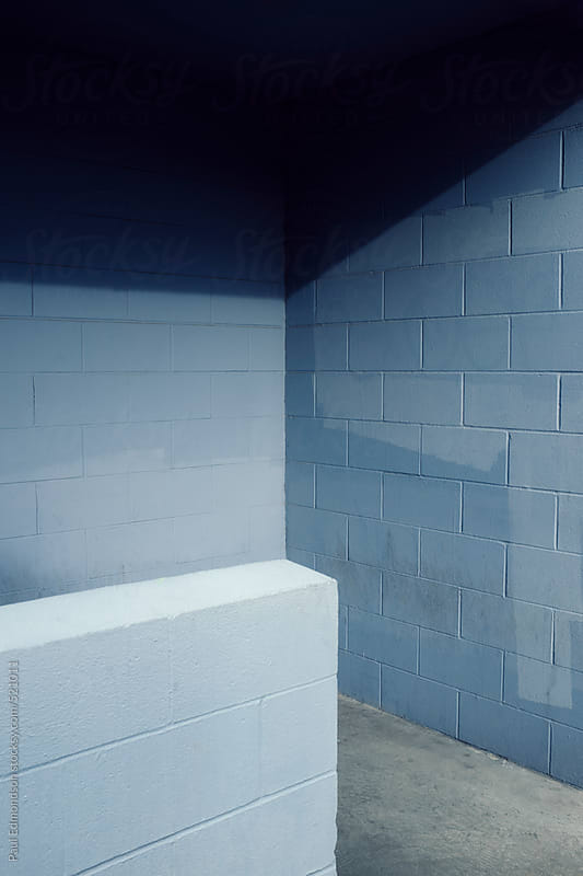Painted blue cinderblock wall with shadow by Paul Edmondson for Stocksy United