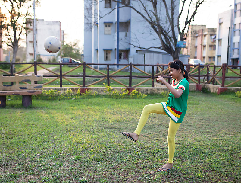 A girl plays football in a park alone  by PARTHA PAL for Stocksy United