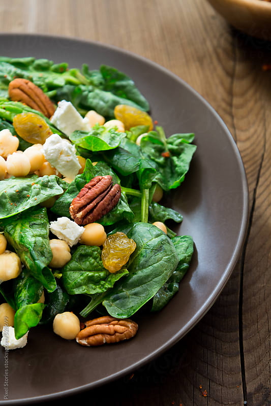 Food: spinach salad with chickpea, pecans and raisins by Pixel Stories for Stocksy United