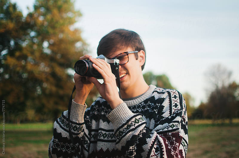 A young man taking a picture with a film camera by Chelsea Victoria for Stocksy United
