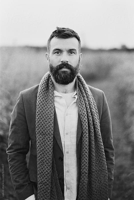 Black and white portrait of a handsome man with a beard standing in a field by Jakob for Stocksy United