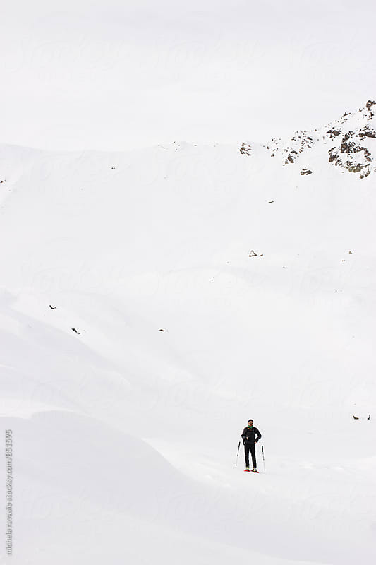 Hiker observing the snowy landscape of the mountain by michela ravasio for Stocksy United