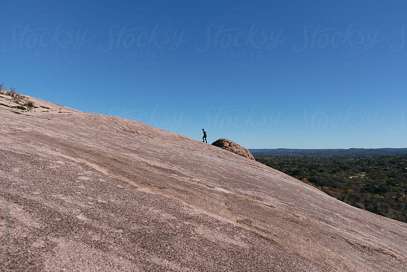 Girl hiking up granite mountain, Texas by Jeremy Pawlowski for Stocksy United