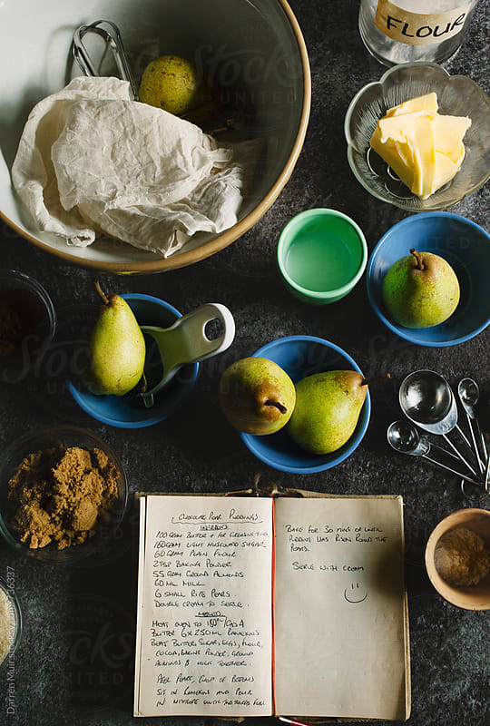 Recipe book surrounded by ingredients on a table. by Darren Muir for Stocksy United