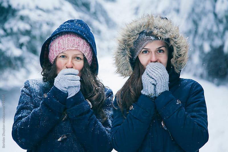 Girlfriends in cap, scarf and gloves feeling cold by Borislav Zhuykov for Stocksy United