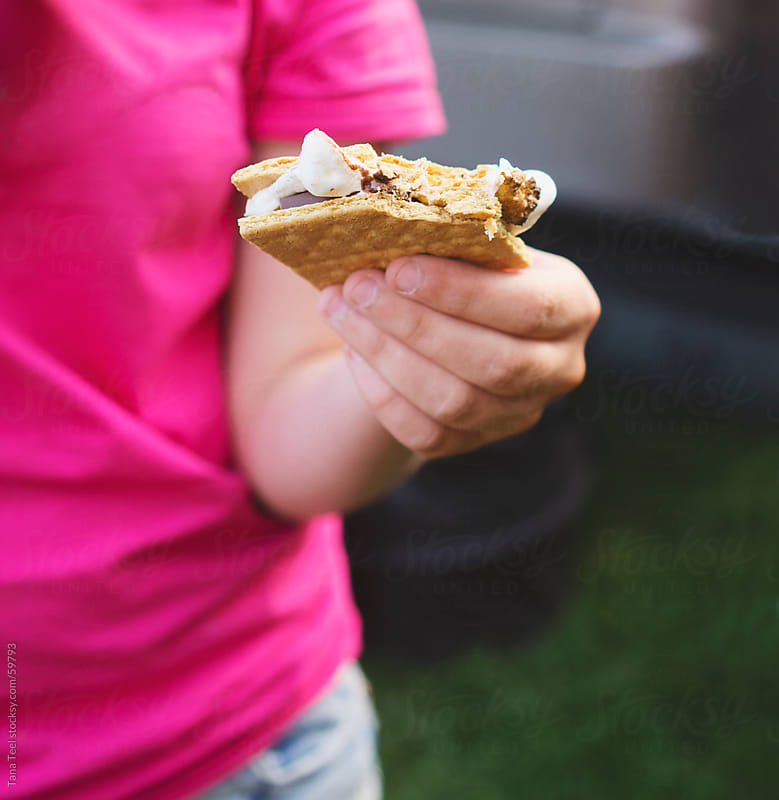 A young woman holds a melted marshmallow, chocolate and cracker by Tana Teel for Stocksy United