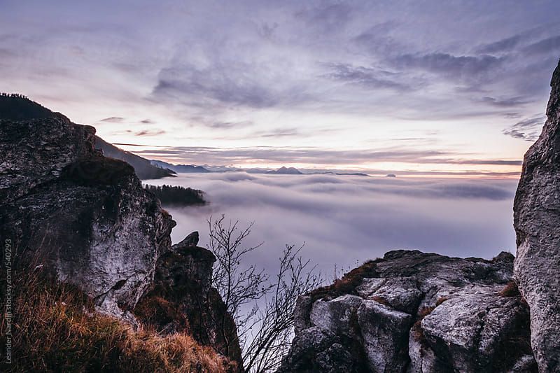sunset in the mountains above the sea of fog  by Leander Nardin for Stocksy United