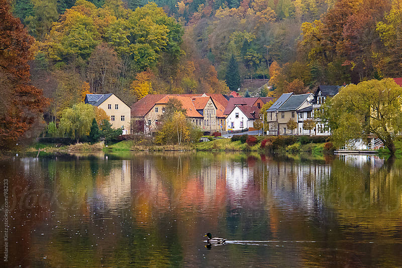 Village in autumn at a river, taken in Thuringia, Germany by Melanie Kintz for Stocksy United