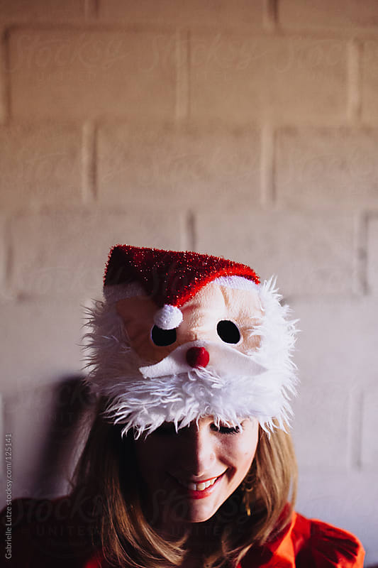 Pretty Girl in Santa Mask by Gabrielle Lutze for Stocksy United