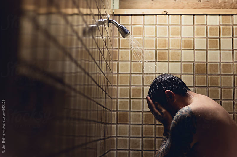 A handsome tattoo'd man washes his face in the shower by Rachel Bellinsky for Stocksy United