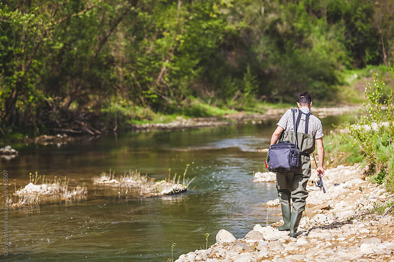Fisherman with Equipment Bag Walking on a Bank of a Small River by Giorgio Magini for Stocksy United