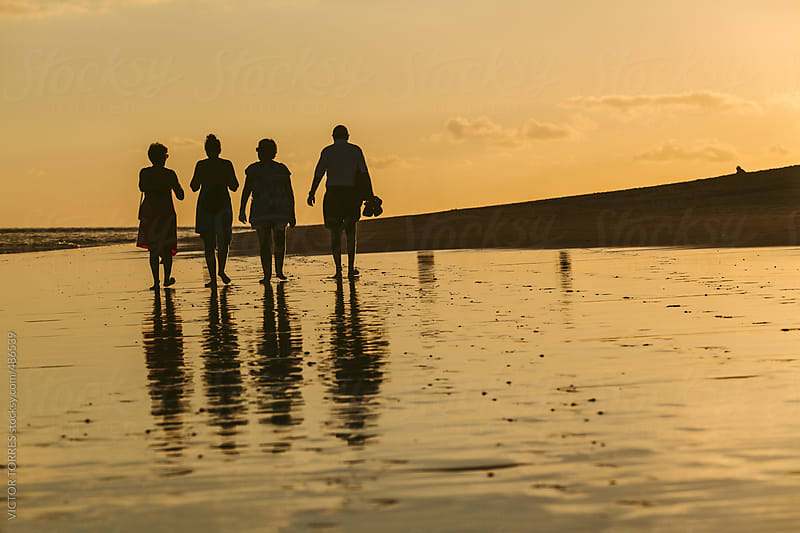 Family Having a Walk at the Beach with a Beautiful Sunset by VICTOR TORRES for Stocksy United