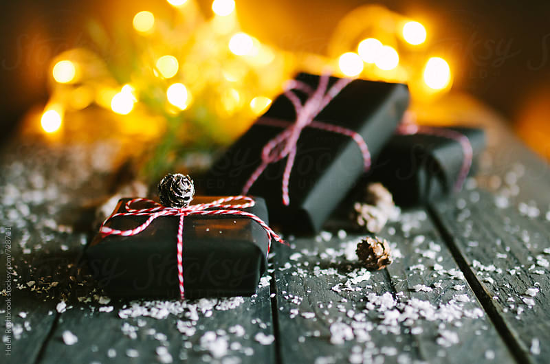 Christmas presents wrapped in black paper with red and white twine. by Helen Rushbrook for Stocksy United