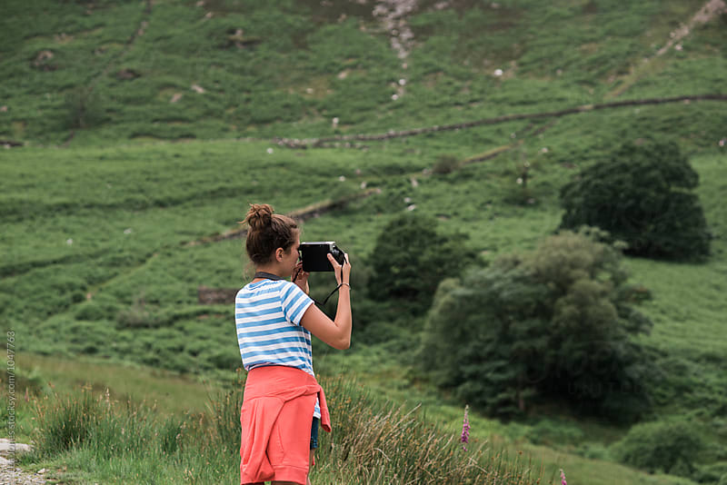 young woman taking a photo in the mountains by Léa Jones for Stocksy United
