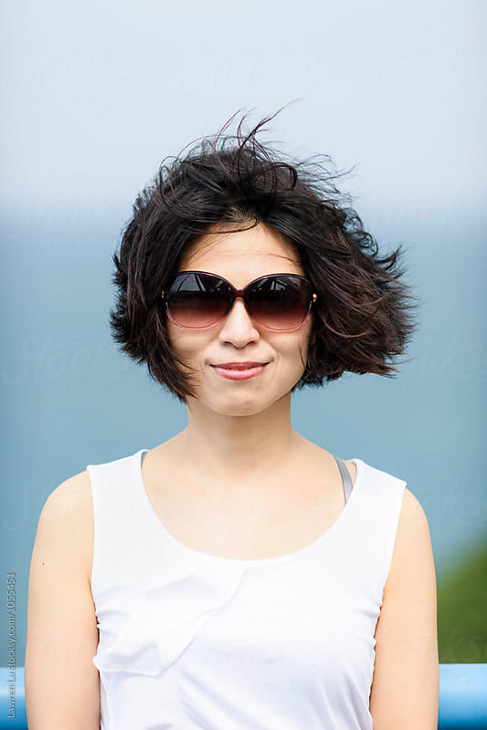 Cheerful Asian woman in sunglasses with windy hair by Lawren Lu for Stocksy United