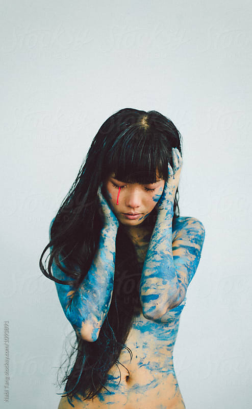 Beautiful blue woman crying in bright pink by Nabi Tang for Stocksy United