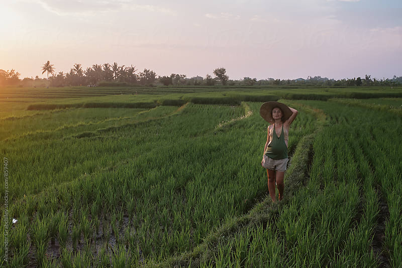 Woman Walking at Sunset In A Green Field by Alexander Grabchilev for Stocksy United