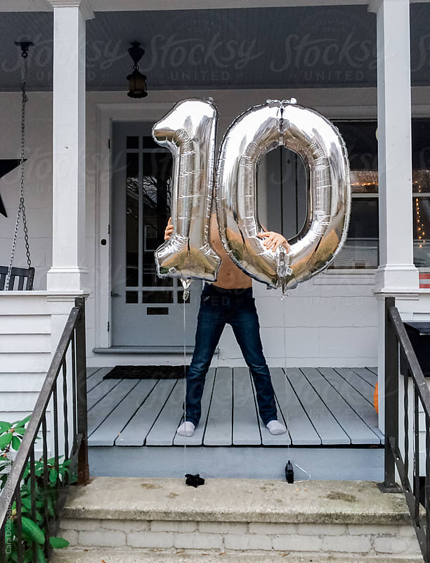 Boy celebrates his 10th birthday with balloons by Cara Slifka for Stocksy United