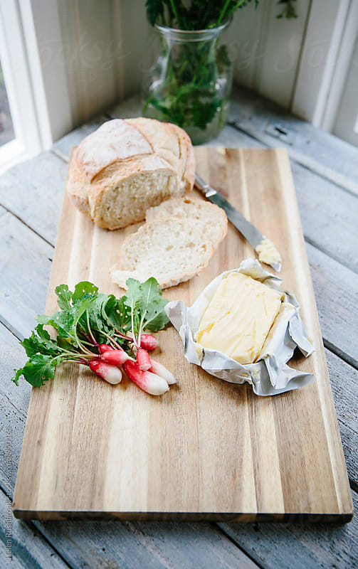 Bread, grass-fed butter and French Breakfast radishes on a board by Helen Rushbrook for Stocksy United