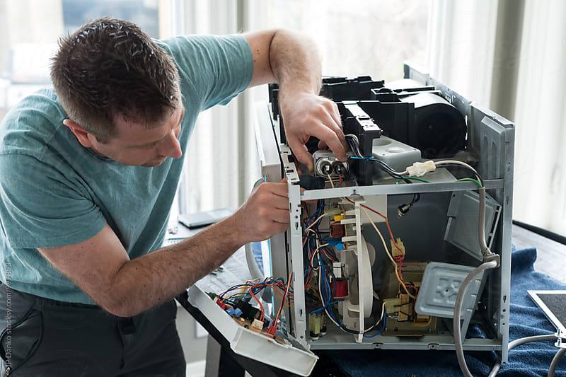 Man Fixing Broken Microwave Oven Appliance In Kitchen by JP Danko for Stocksy United