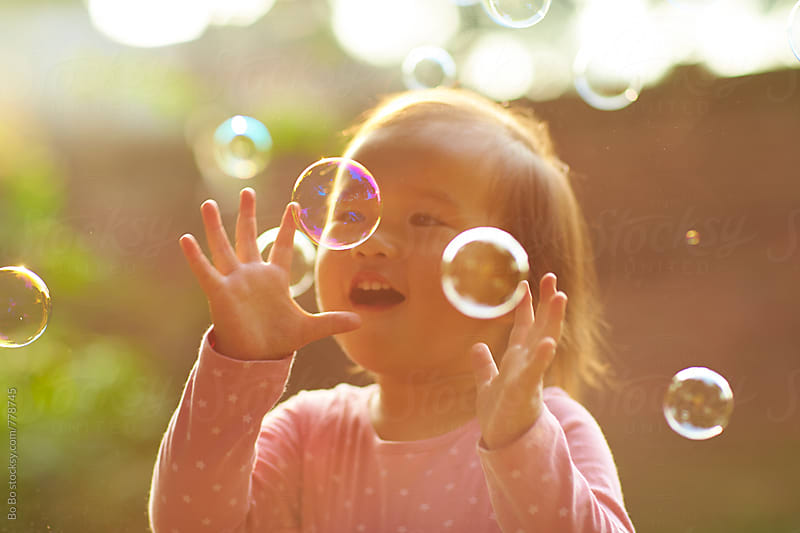 close up of one happy little asian girl playing with soap bubble by Bo Bo for Stocksy United