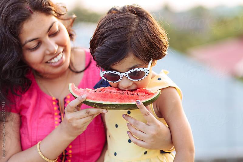 Mother feeding her daughter with watermelon outdoors,summer fun by Saptak Ganguly for Stocksy United
