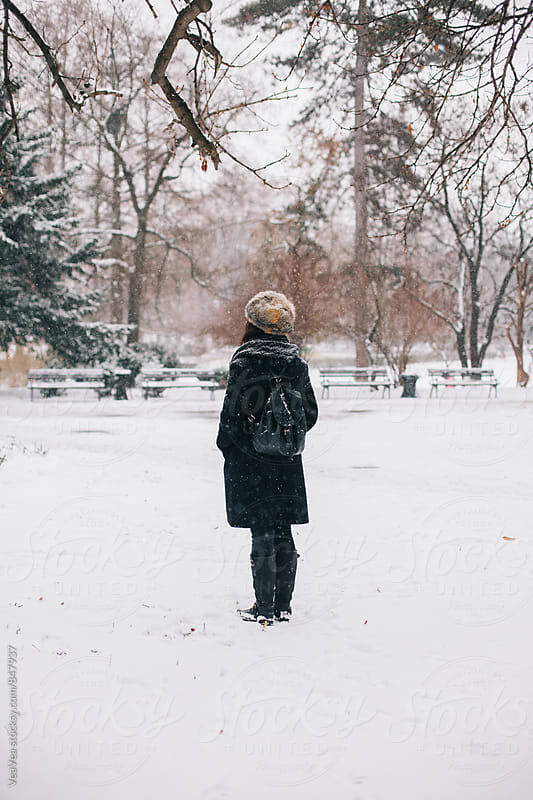 Stylish woman standing in the park during snowy day  by VeaVea for Stocksy United