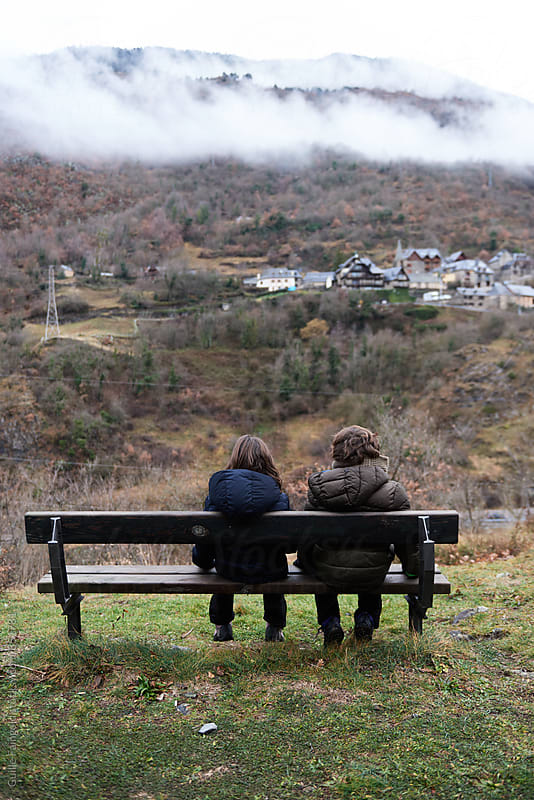 Two children sitting on bench while dog walking near them by Guille Faingold for Stocksy United