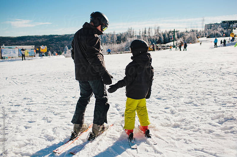 father teaching child how to ski by Kelly Knox for Stocksy United
