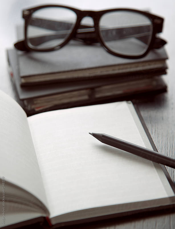 blank notebook and glasses by Sonja Lekovic for Stocksy United