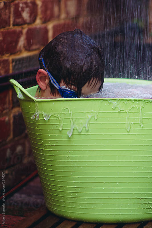 Boy sitting in a plastic bucket under an outdoor shower by Angela Lumsden for Stocksy United