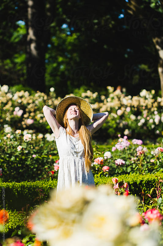 Beautiful young woman relaxing in a flower garden in a sunny day by michela ravasio for Stocksy United