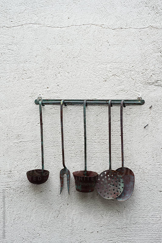 old kitchen utensils on a wall as art by Gillian Vann for Stocksy United