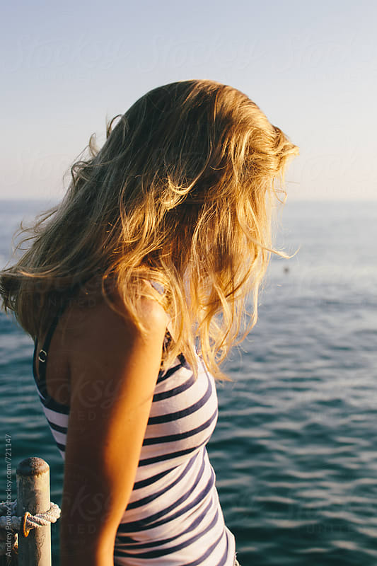 Woman looking at sea at sunset by Andrey Pavlov for Stocksy United