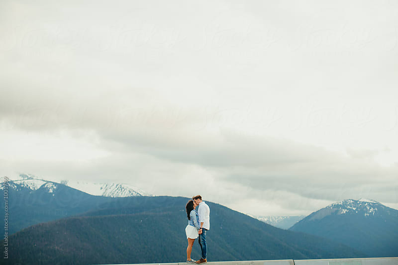 Couple embrace on top of mountain by Luke Liable for Stocksy United