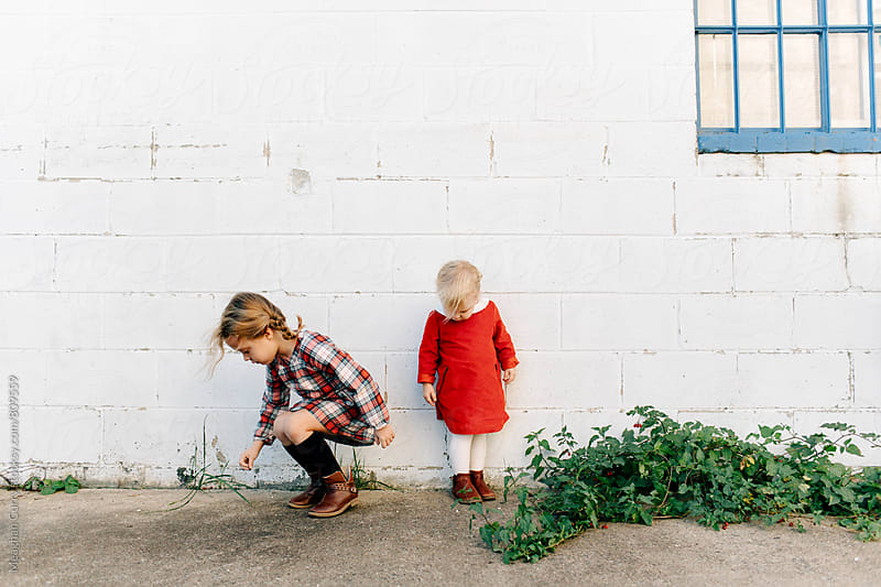 portraits of two young sisters dressed in holiday colors by Meaghan Curry for Stocksy United