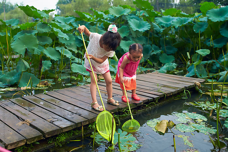 little girls trying to catch fish by the lake by Bo Bo for Stocksy United