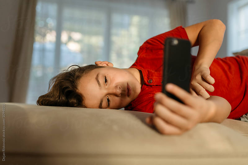 Boy watching videos on mobile phone. by Dejan Ristovski for Stocksy United