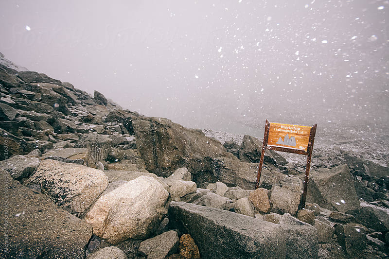 Snowstorm in Torres del Paine with wooden sign on rocks by Alejandro Moreno de Carlos for Stocksy United