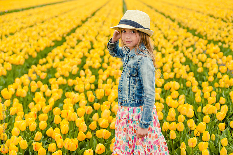 Little girl in yellow tulip field looking over her shoulder by Cindy Prins for Stocksy United