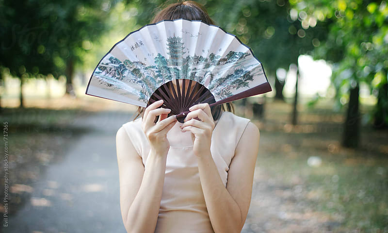 Portrait of anonymous female model with fan by Evil Pixels Photography for Stocksy United